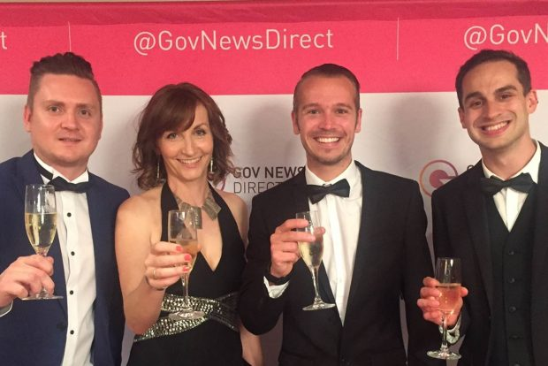 Photo of Jo and colleagues at the @GovNewsDirect awards. The group are all smartly dressed and holding up glasses of champagne. Theyre standing in front of a banner which says @GovNewsDirect