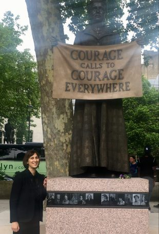 Amirit stands next to the recently- erected statue in Parliament Square. Amrit is wearing a dark suit