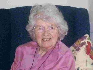 A photograph of Emma's Nan sitting in a blue high-backed chair, wearing a pink blouse.