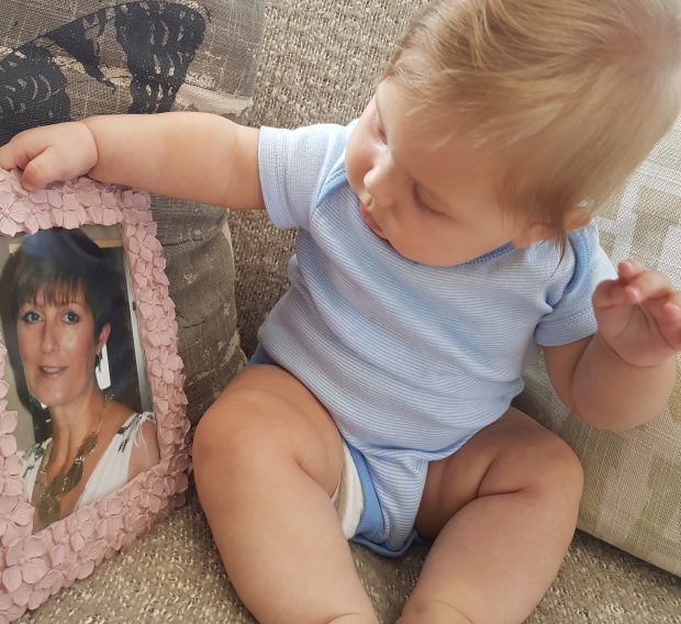 A young toddler sits in a cream coloured chair holding and looking at a framed picture of Charlotte's mum.