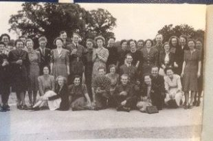 An old, black and white photograph of a group of 30-or-so people in 1940's clothing posing and smiling. Some are crouched or sat on the ground whilst the others stand behind them. The photo was taken outside on a lawn and there are tree-tops in the background.