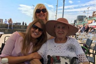 A photo of Georgia with her mum and grandmother on a sunny holiday.