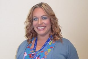 A head and shoulders shot of Emma, who has shoulder-length curly blonde hair, is smiling broadly and is wearing a blue flowery blouse.