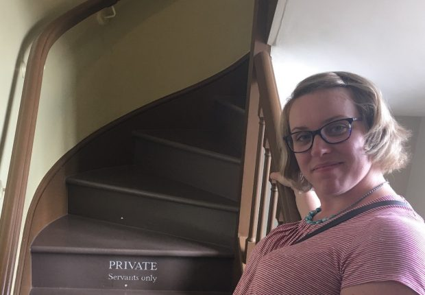 Profile picture of Jess standing at the bottom of a staircase. The staircase has a sign which says 'PRIVATE - servants only'