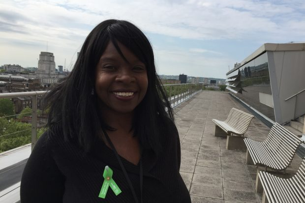 Picture of Karen standing on the roof of a building. She has a big smile and is wearing a green ribbon on her jacket
